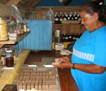 Hand wrapping the fresh bars of soap using recycled paper.